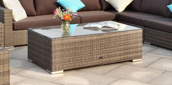 Stort rektangulært rotting bord med glassplate på en uteplass med blomster og et magasin. Puter i tilhørende utendørs sofagruppe. Sommer på terrassen   SparMax